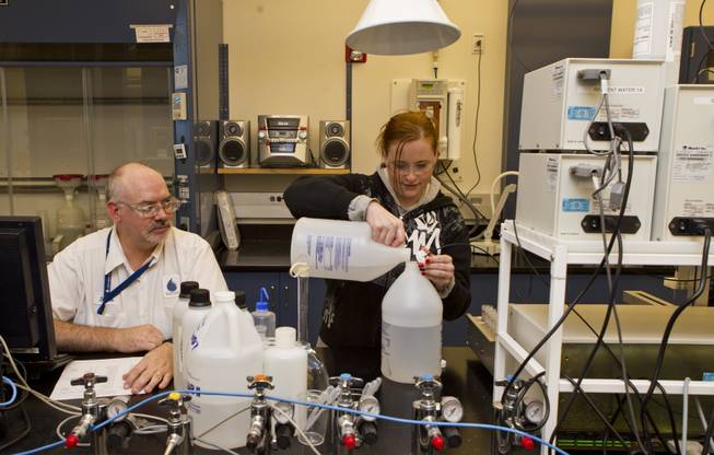 Steve George and Jennifer McCarville conduct fluoride detection tests in water samples at the inorganic lab within the SNWA's massive testing facility out near Lake Mead on Wednesday, July 9, 2014.