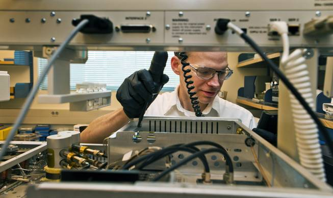 Analytical chemist Matthew Desautel makes a small electrical repair on a piece of equipment in his lab within the SNWA's massive testing facility out near Lake Mead on Wednesday, July 9, 2014.