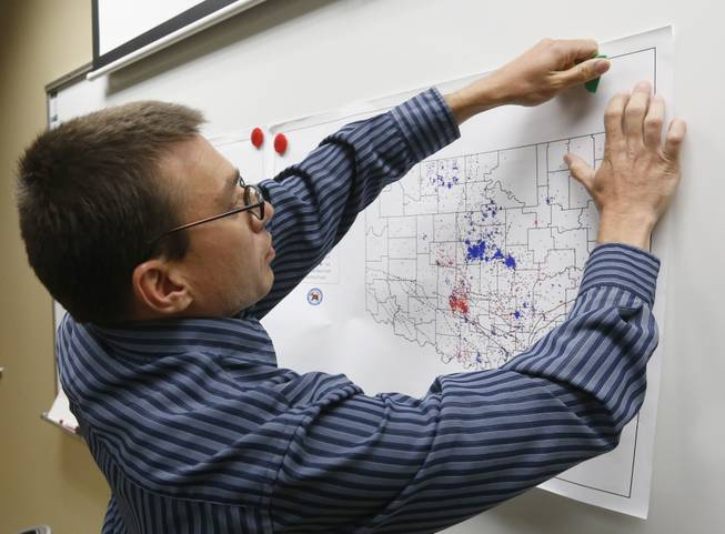 In this June 26, 2014 file photo, Austin Holland, research seismologist at the Oklahoma Geological Survey, hangs up a chart depicting earthquake activity at their offices at the University of Oklahoma in Norman, Okla. States where hydraulic fracturing is taking place have seen a surge in seismic activity, raising suspicions that the unconventional drilling method, especially the wells in which the industry disposes of its wastewater, could be to blame.