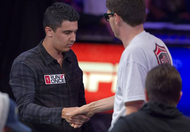 Craig McCorkell of Britain shakes hands with Mark Newhouse after being knocked out of the World Series of Poker $10,000 buy-in No-limit Texas Hold 'em main event at the Rio Monday, July 14, 2014. McCorkell finished in 13th place.