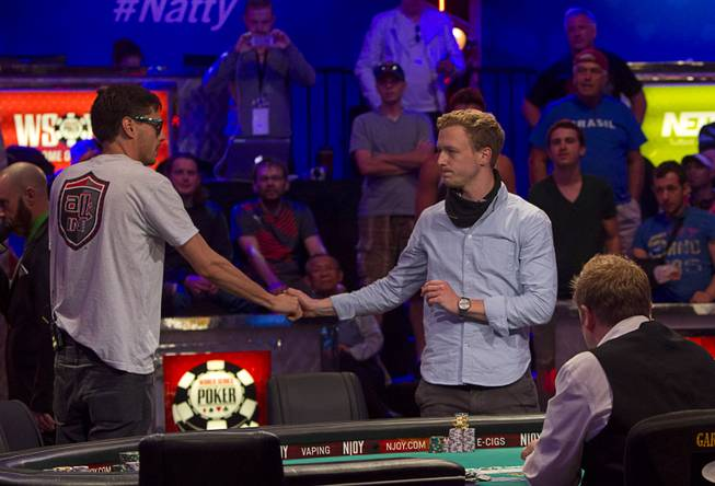 Mark Newhouse, left, shakes hands with Maximilian Senft of Austria after knocking Senft out of the World Series of Poker $10,000 buy-in No-limit Texas Hold 'em main event at the Rio Monday, July 14, 2014.