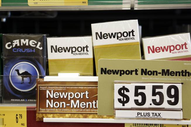 Camel, a Reynolds American brand, and Newport, a Lorillard brand, cigarettes are displayed for sale, Tuesday, July 15, 2014, in Doral, Fla.