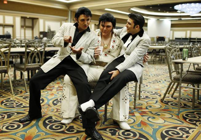In this July 12, 2014, photo, from left, Daniel Jenkins, Tyler James and Jacob Roman joke around during the Las Vegas Elvis Festival in Las Vegas. The three, along with other Elvis tribute artists, performed in a competition at the convention.