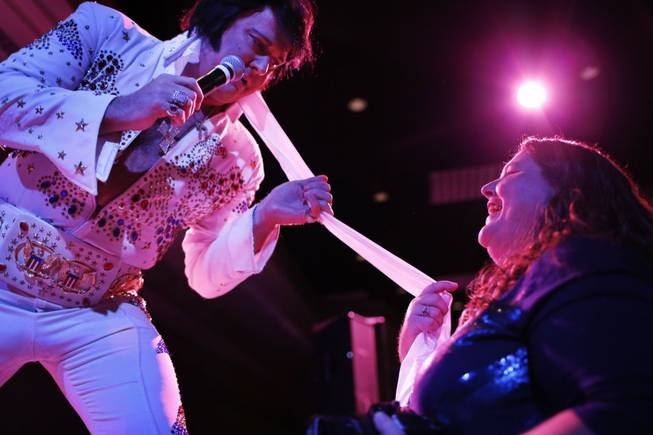 In this July 12, 2014, photo, Elvis tribute artist Jim Westover, left, of Arizona City, Ariz., gives a scarf to fan Juanita Curtice, of Woodbridge, Va., during the Las Vegas Elvis Festival in Las Vegas. Some three dozen Elvis tribute artists took their gyrating hips and curled lips to the stage over the weekend to see who could do the most convincing portrayal.
