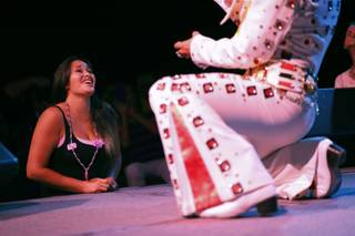In this July 12, 2014, photo, Yvonne Garcia, of Midland, Texas, watches an Elvis tribute artist perform during the Las Vegas Elvis Festival in Las Vegas. Some three dozen Elvis tribute artists took their gyrating hips and curled lips to the stage over the weekend to see who could do the most convincing portrayal.