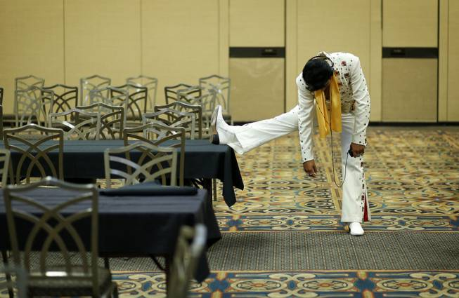 In this July 12, 2014, photo, Elvis tribute artist Joseph Hall, of Branson, Mo., stretches before performing at the Las Vegas Elvis Festival in Las Vegas. Some three dozen Elvis tribute artists took their gyrating hips and curled lips to the stage over the weekend to see who could do the most convincing portrayal.