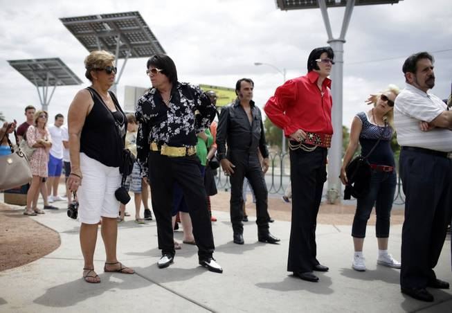 "In this July 10, 2014 photo, Elvis tribute artists participating in the Las Vegas Elvis Festival wait in line to take pictures in front of the ""Welcome to Las Vegas"" sign in Las Vegas. Several of the tribute artists took a bus tour around Las Vegas during the convention."