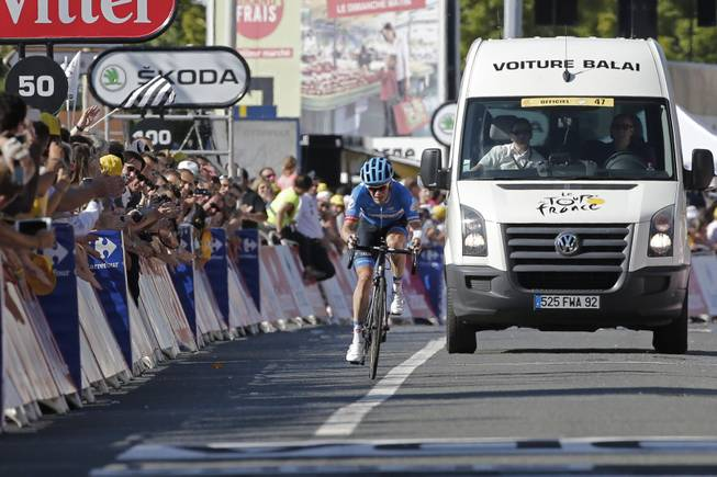"Andrew Talansky of the U.S. is accompanied by the ""voiture balai"" or ""broom wagon"" which sweeps up riders lagging behind as he arrives in the last 50 meters of the race of the eleventh stage of the Tour de France cycling race over 187.5 kilometers (116.5 miles) with start in Besancon and finish in Oyonnax, France, Wednesday, July 16, 2014."