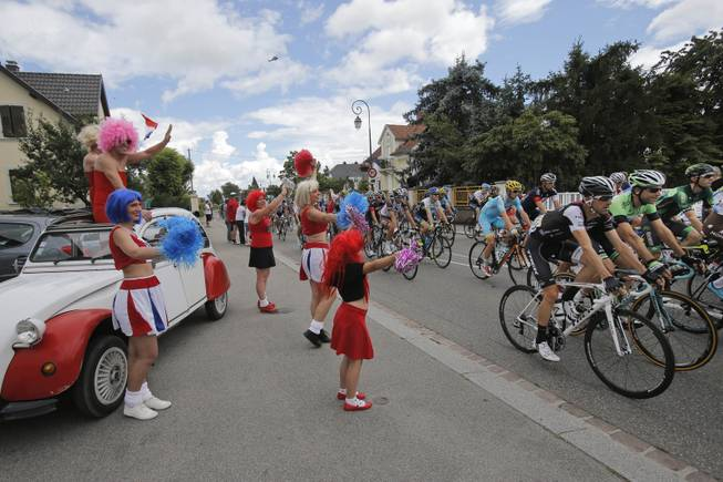 Cheerleaders with a Citroen 2CV classic car greet the pack during the tenth stage of the Tour de France cycling race over 161.5 kilometers (100.4 miles) with start in Mulhouse and finish in La Planche des Belles Filles, France, Monday, July 14, 2014.