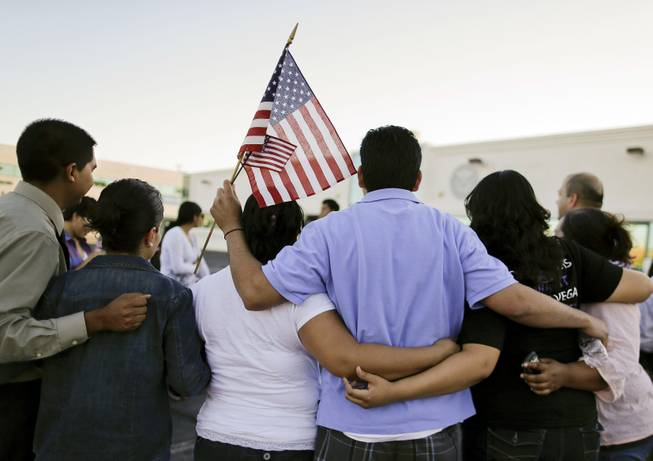 Martin Martinez, center, and his wife, Blanca Martinez, third from left, gather for a photo outside the Immigration and Customs Enforcement offices during an immigration vigil, Wednesday, April 10, 2013, in Las Vegas. During the process in which Blanca Martinez, a U.S. citizen, applied for a petition for her husband to obtain a Green Card, Martin was detained by ICE officials for nearly two weeks and nearly deported back to El Salvador before being released. The vigil was held to honor all who have been detained or deported by ICE.