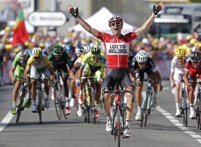 France's Tony Gallopin manages to stay ahead of the spring pack, rear, as he crosses the finish line to win the eleventh stage of the Tour de France cycling race over 187.5 kilometers (116.5 miles) with start in Besancon and finish in Oyonnax, France, Wednesday, July 16, 2014.
