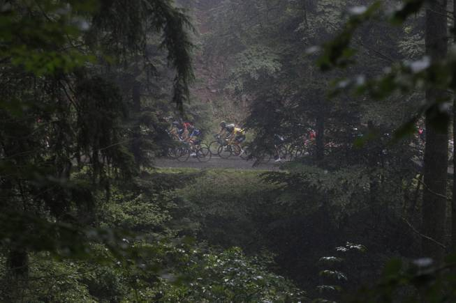 The pack rides through the Vosges mountains during the tenth stage of the Tour de France cycling race over 161.5 kilometers (100.4 miles) with start in Mulhouse and finish in La Planche des Belles Filles, France, Monday, July 14, 2014.
