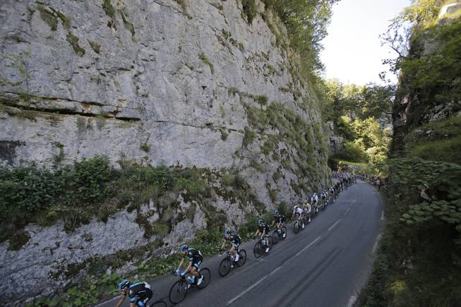 The pack passes during the eleventh stage of the Tour de France cycling race over 187.5 kilometers (116.5 miles) with start in Besancon and finish in Oyonnax, France, Wednesday, July 16, 2014.