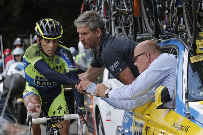 Spain's Alberto Contador gets assistance from his team after crashing during the tenth stage of the Tour de France cycling race over 161.5 kilometers (100.4 miles) with start in Mulhouse and finish in La Planche des Belles Filles, France, Monday, July 14, 2014. Contador withdrew from the race as a result of the crash, right is his team manager Bjarne Riis of Denmark.