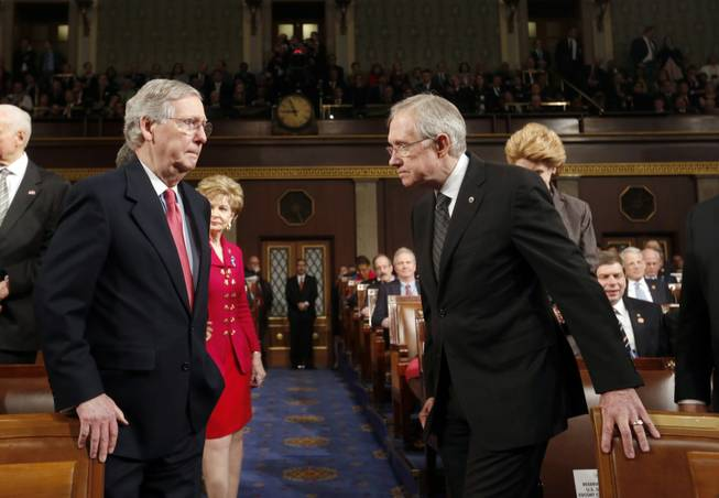 Senate Minority Leader Mitch McConnell, left, and Senate Majority Leader Harry Reid head to the front of the chamber before President Barack Obama delivers his State of the Union speech on Capitol Hill in Washington on Tuesday, Jan. 28, 2014.
