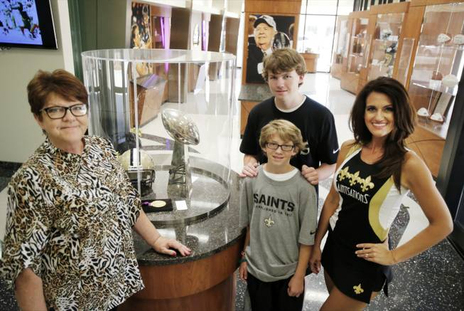 New Orleans Saints cheerleader Kriste Lewis, right, her sons Jake, 14, and Rob, 11, center, and her mother, Vassie Owens, left, poses for a photograph at the NFL football team's training facility in Metairie, La., on Wednesday, July 16, 2014. Lewis is one of only two NFL cheerleaders in her 40s. The other dancer is 45-year-old Laura Vikmanis, who has been with the Cincinnati Bengals dance team, the Ben-Gals, since making the squad at age 40.