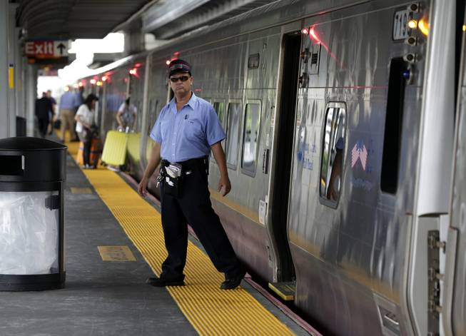 A conductor checks the platform at the Jamaica station of the Long Island Rail Road, in the Queens borough of New York, on Wednesday, July 16, 2014. Negotiations aimed at avoiding a walkout at the nation's largest commuter railroad resumed Wednesday after Gov. Andrew Cuomo prodded both sides to find an agreement that would keep 300,000 daily riders from being forced to find alternate ways of getting in and out of New York City.