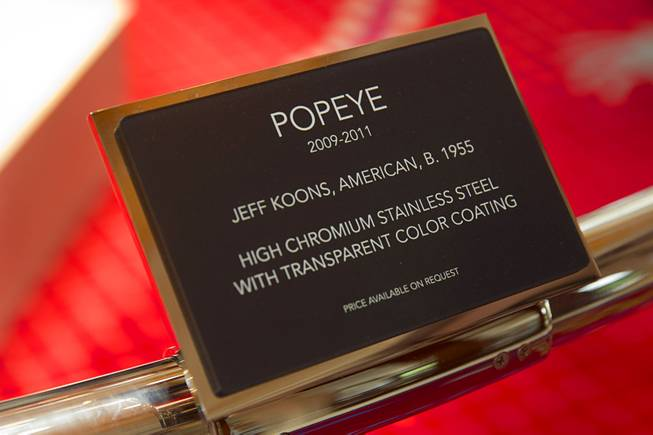 A plaque gives information on the Popeye sculpture in the Wynn Esplanade Thursday, July 17, 2014. The stainless steel sculpture, by American artist Jeff Koons, was purchased at auction for $28.2 million.