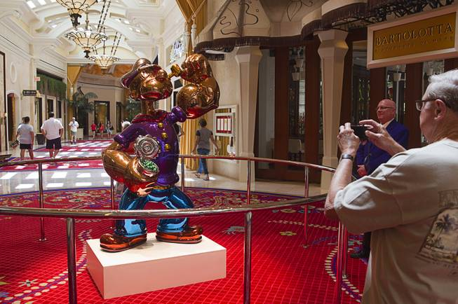 A man takes a photo of the Popeye sculpture in the Wynn Esplanade Thursday, July 17, 2014. The stainless steel sculpture, by American artist Jeff Koons, was purchased at auction for $28.2 million.
