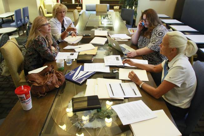 From left, Paula Newman, Alexandra Davis, Susan Lara and Brenda Gunsallus work on their application for a medical marijuana dispensary and production facility Wednesday, July 16, 2014.