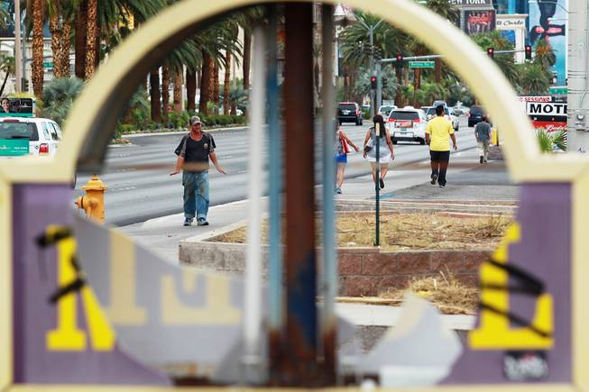 Pedestrians are seen through a broken sign at the Laughing Jackalope on the south end of the Strip Tuesday, July 15, 2014.