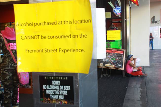 A woman drinks from a can in a bag while sitting outside a store at the Fremont Street Experience Thursday, July 17, 2014.