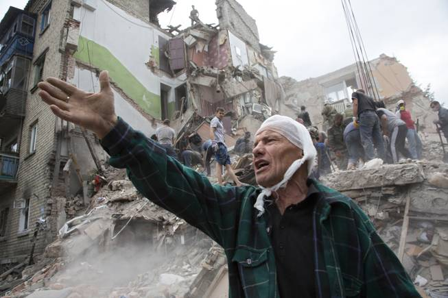 AP10ThingsToSee - Igor Chernetsov, whose wife was killed in a building demolished by an airstrike, gestures near the collapsed structure in Snizhne, 100 kilometers east of Donetsk, eastern Ukraine, Tuesday, July 15, 2014. At least nine civilians were killed in the attack, rescue workers said.