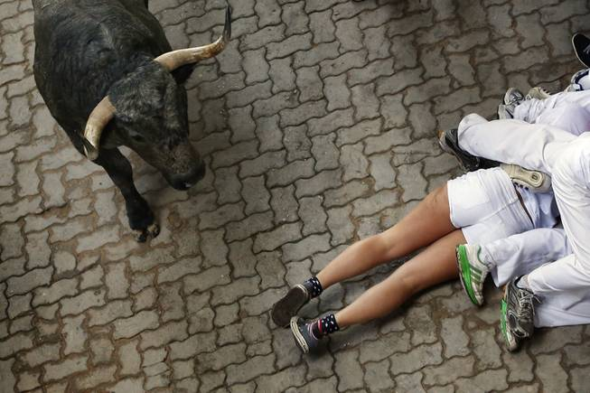 AP10ThingsToSee - Fallen revelers lie on the ground as a fighting bull runs by during the running of the bulls at the San Fermin festival, in Pamplona, Spain, Sunday, July 13, 2014.