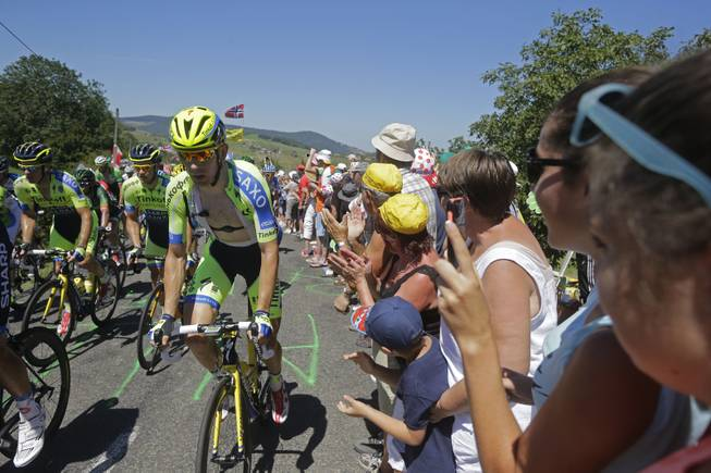 Spectators applause as the pack with team Tinkoff Saxo riders climbs during the twelfth stage of the Tour de France cycling race over 185.5 kilometers (115.3 miles) with start in Bourg-en-Bresse and finish in Saint-Etienne, France, Thursday, July 17, 2014.
