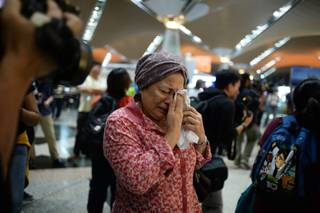 A woman reacts to news regarding a Malaysia Airlines plane that crashed in eastern Ukraine at Kuala Lumpur International Airport in Sepang, Malaysia, Friday, July 18, 2014.  Ukraine said a passenger plane carrying 295 people was shot down Thursday as it flew over the country, and both the government and the pro-Russia separatists fighting in the region denied any responsibility for downing the plane.