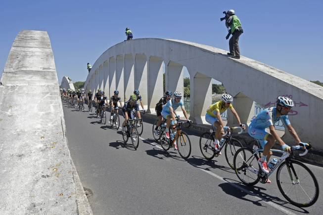 Photographers take pictures of the pack with Italy's Vincenzo Nibali, wearing the overall leader's yellow jersey, as it passes over a bridge during the twelfth stage of the Tour de France cycling race over 185.5 kilometers (115.3 miles) with start in Bourg-en-Bresse and finish in Saint-Etienne, France, Thursday, July 17, 2014.