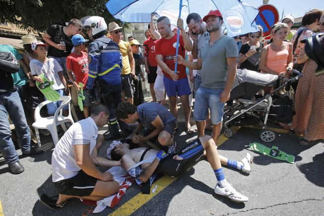 Spectators shield Spain's David De La Cruz Melgarejo from the sun after he crashed when riding in the breakaway in Oingt, during the twelfth stage of the Tour de France cycling race over 185.5 kilometers (115.3 miles) with start in Bourg-en-Bresse and finish in Saint-Etienne, France, Thursday, July 17, 2014. De La cruz had to withdraw from the race because of his injuries.