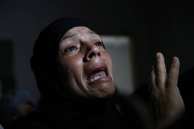 AP10ThingsToSee - A Palestinian mourner cries after the bodies of Mousa Abu Muamer, 56, and his son Saddam, 27, were brought in for their funeral on Monday, July 14, 2014, in the Gaza Strip. The two were killed in an overnight Israeli missile strike at their house in the outskirts of the town of Khan Younis, southern Gaza Strip.