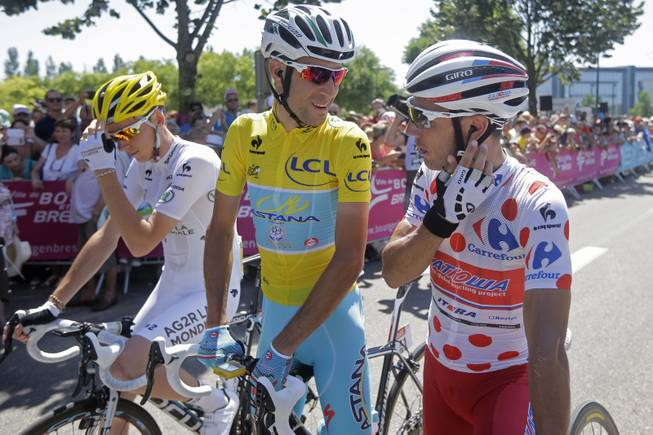 Italy's Vincenzo Nibali, wearing the overall leader's yellow jersey, talks to Spain's Joaquim Rodriguez, wearing the best climber's dotted jersey, as they wait with France's Romain Bardet, wearing the best young rider's white jersey, for the start of the twelfth stage of the Tour de France cycling race over 185.5 kilometers (115.3 miles) with start in Bourg-en-Bresse and finish in Saint-Etienne, France, Thursday, July 17, 2014.
