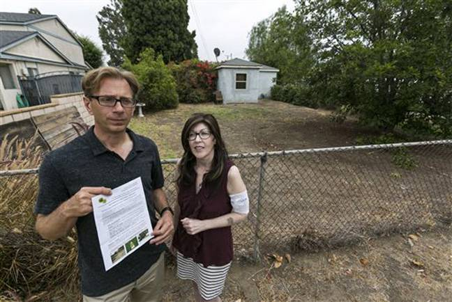 Michael Korte and his wife, Laura Whitne scaled back watering due to drought but received a letter from the city of Glendora warning they could face fines if they don't get their brown lawn green again. They're shown outside their house on Thursday, June 17, 2014.