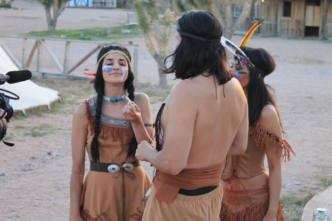 "Penny Pibbets, joined by crossbow artists Ottavio and Naomi Gesmundo, enjoys what appears to be a peace pipe during the video shoot for Melody Sweets' ""Shoot 'em Up"" at Grand Canyon Ranch on April 22, 2014."