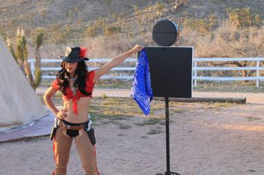 "Melody Sweets lets a scarf dangle as a target during the video shoot for Sweets' ""Shoot 'em Up"" at Grand Canyon Ranch on April 22, 2014."