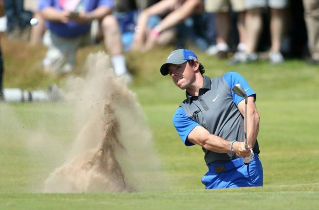 Rory McIlroy of Northern Ireland plays out of a bunker on the 16th hole during the first day of the British Open at the Royal Liverpool golf club in Hoylake, England, on Thursday, July 17, 2014.