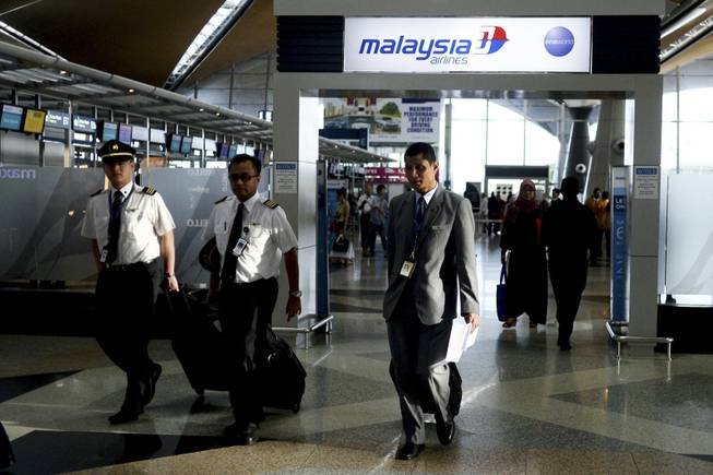 Malaysia Airlines flight crews arrive at Kuala Lumpur International Airport in Sepang, Malaysia, on Friday, July 18, 2014. The Malaysia Airlines Boeing 777-200 that was shot down over war-torn eastern Ukraine on Thursday was carrying 298 people from at least nine countries.
