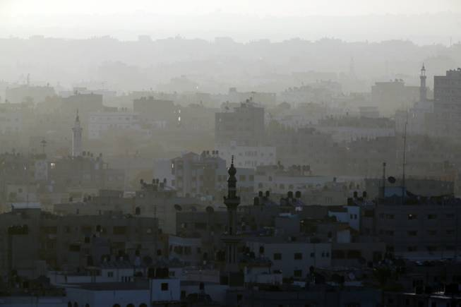 A hazy Gaza City is seen in the northern Gaza Strip early Friday, July 18, 2014. The heavy thud of tank shells, often just seconds apart, echoed across the Gaza Strip early Friday as thousands of Israeli soldiers launched a ground invasion, escalating a 10-day campaign of heavy air bombardments to try to destroy Hamas' rocket-firing abilities and the tunnels militants use to infiltrate Israel.