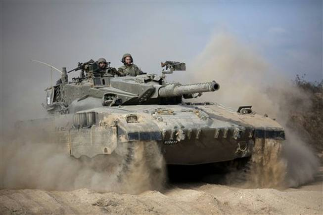 An Israeli tank moves into position near the Israel and Gaza border, Friday, July, 18, 2014. Israeli troops pushed deeper into Gaza on Friday to destroy rocket-launching sites and tunnels. Israel launched the operation late Thursday.
