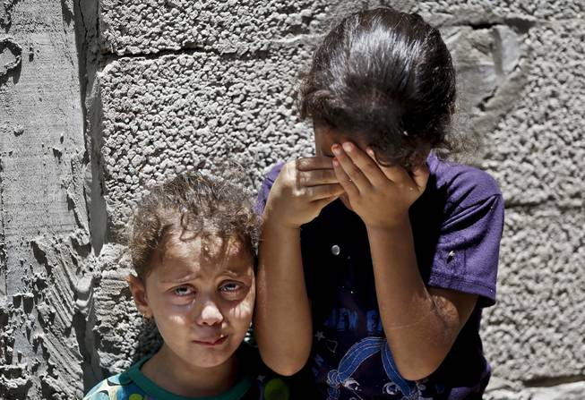 In this Thursday, July 17, 2014, file photo, Palestinian siblings Maria Abdel Aal, 4, right, and Misk, 3, left, cry as the body of their relative Bashir Abdel Aal, killed in an overnight Israeli missile strike in Rafah, southern Gaza Strip, is carried away from the family house, during his funeral. Minors make up almost one-fifth of those killed in Israel's 11-day bombardment of Hamas targets in densely populated Gaza, where half the population is under the age of 18.