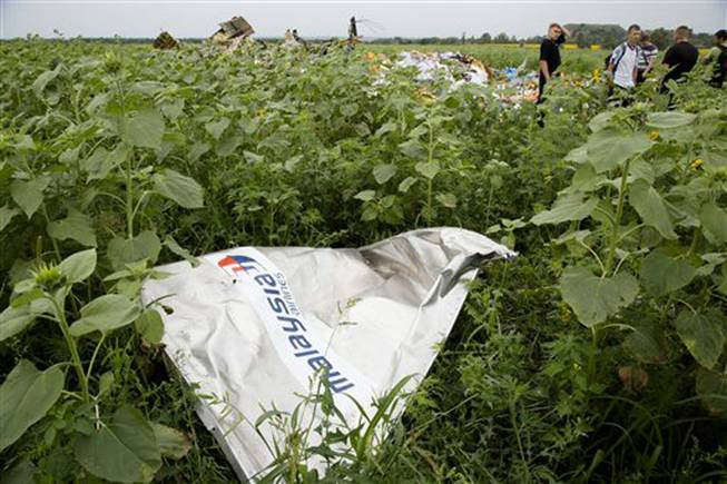 A piece of plane wreckage with Malaysia Airlines' logo lies in the grass as a group of Ukrainian coal miners searches the crash site near the village of Rozsypne, Ukraine, Friday, July 18, 2014. The Malaysian plane ended up in burning pieces Thursday, killing all 298 aboard.