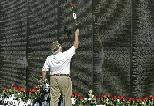 Maj. Wayne Witter, of Dunwoody, Ga., holds a red rose in 2007 as he touches the name of a fallen comrade at the Vietnam Veterans Memorial in Washington. The names of 74 sailors who died in a ship collision in 1969 haven't been added because their ship was outside the official war zone.