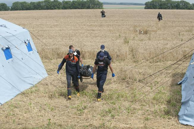 Emergency workers carry a stretcher with a victim's body in a bag at the crash site of a Malaysia Airlines jet near the village of Hrabove, eastern Ukraine, on Saturday, July 19, 2014. Ukraine accused Russia on Saturday of helping separatist rebels destroy evidence at the crash site of a Malaysia Airlines plane shot down in rebel-held territory — a charge the rebels denied.