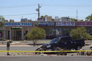 A Metro crime scene analyst takes a photo at a fatal accident on Sahara Avenue near Valley View Boulevard Sunday, July 20, 2014. A man who was apparently working on the sidewalk was killed in the accident.