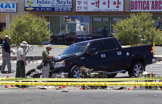 A Metro Police team investigate a fatal accident on Sahara Avenue near Valley View Boulevard Sunday, July 20, 2014. A man who was apparently working on the sidewalk was killed in the accident.