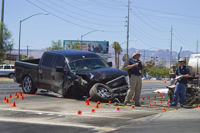 Metro Police investigators take measurements at a fatal accident on Sahara Avenue near Valley View Boulevard Sunday, July 20, 2014. A man who was apparently working on the sidewalk was killed in the accident.