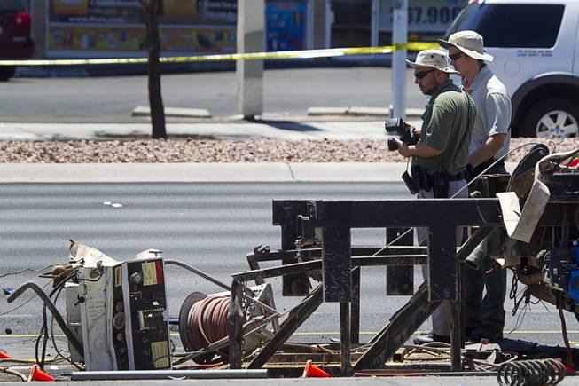 Metro Police crime scene analysts look over a fatal accident scene on Sahara Avenue near Valley View Boulevard Sunday, July 20, 2014. A man who was apparently working on the sidewalk was killed in the accident.