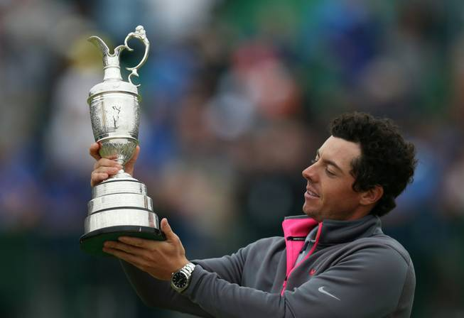 Rory McIlroy holds up the Claret Jug trophy after winning the British Open golf championship at Royal Liverpool Golf Club in Hoylake, England, on Sunday, July 20, 2014.